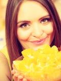 Woman holds bowl full of sliced orange fruits Stock Photos