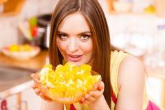 Woman holds bowl full of sliced orange fruits Stock Photography