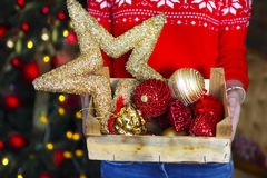 A woman holds a box with a lot of Christmas decorations Stock Image