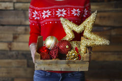 A woman holds a box with a lot of Christmas decorations Stock Photography