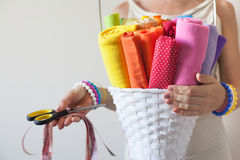 A woman holds bright colored fabrics for sewing and scissors. Colored fabrics for sewing Royalty Free Stock Photography