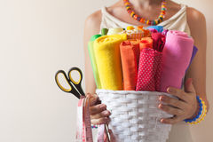 A woman holds bright colored fabrics for sewing and scissors. Fabrics for sewing lie in a white basket. A woman holding a basket Stock Image