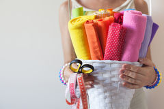 A woman holds bright colored fabrics for sewing and scissors. Fabrics for sewing lie in a white basket. A woman holding a basket Stock Photography