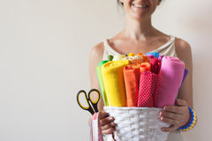 A woman holds bright colored fabrics for sewing and scissors. Sewing Fabrics lie in a white basket. A woman holding a basket Royalty Free Stock Images