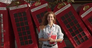 A woman holds a British flag and a book and bounces with them. Joy fun. education abroad, language learning. stock video footage