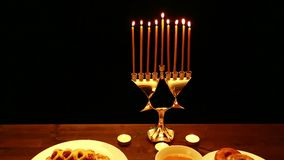 A woman holds a burning candle in her hand with which she lights candles in a candlestick for the Hanukkah. a woman lights candles. From the first candle from