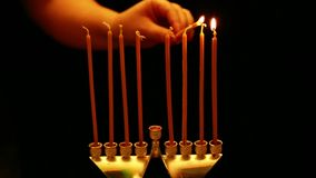 A woman holds a burning candle in her hand from which she lights candles in a Hanukkah lamp. a woman lights candles from the first. To the third from right to