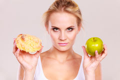 Woman holds cake and fruit in hand choosing. Woman holds in hand cake sweet bun and apple fruit choosing, trying to resist temptation, make the right dietary stock image