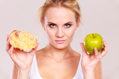 Woman holds cake and fruit in hand choosing Royalty Free Stock Photo