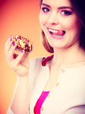 Woman holds cake in hand licking lips Stock Photos