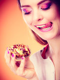 Woman holds cake in hand licking lips Stock Images