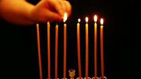 A woman holds a candle in her hand and lights candles in a Hanukkah candlestick. camera movement from right to left. A woman holds a candle in her hand and