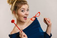 Woman holds carnival accessories on stick royalty free stock photo