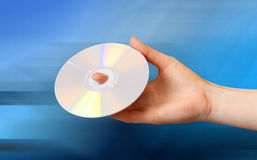 DVD in hand. Woman holds a CD on a blue background Stock Images