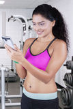 Woman holds cellphone at gym Royalty Free Stock Image