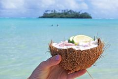 Woman holds Ceviche Dish served in a coconut shell against a isl Royalty Free Stock Photos