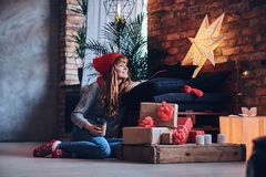 A woman holds a Christmas gift in a living room with loft interi Royalty Free Stock Photos