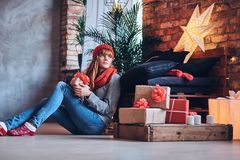 A woman holds a Christmas gift in a living room with loft interi Stock Photos