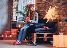 A woman holds a Christmas gift in a living room with loft interior. Royalty Free Stock Image