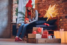 A woman holds a Christmas gift in a living room with loft interior. Royalty Free Stock Photography