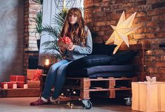 A woman holds a Christmas gift in a living room with loft interior. Stock Images