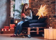 A woman holds a Christmas gift in a living room with loft interior. Stock Photos