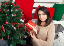 Woman holds Christmas present Stock Photos