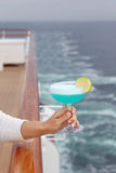 Woman holds cocktail at background of sea Stock Image