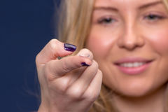 Woman holds a contact lens Stock Images