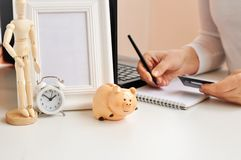 A woman holds a credit card on the background of a piggy Bank, a laptop, a clock, a frame, a notebook and a wooden figure of a man royalty free stock images