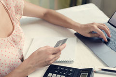 Woman holds a credit card in her hand and works on a laptop or pays for purchases Royalty Free Stock Photos