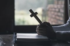 The woman holds the cross and prayes with her scriptures on the table royalty free stock photography