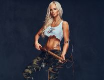 A woman holds crossbow. An attractive blond female dressed in a bra and military pants holds an ancient wooden crossbow over grey background Royalty Free Stock Photography