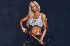 A woman holds crossbow. An attractive blond female dressed in a bra and military pants holds an ancient wooden crossbow over grey background Royalty Free Stock Image