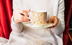 A woman holds a cup of tea or coffee in her hands. Copy space. Selective frame. royalty free stock photos