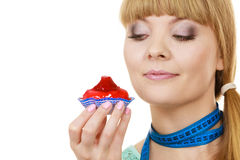 Woman holds cupcake trying to resist temptation. Woman undecided with blue measuring tape around her neck holds in hand cake cupcake, trying to resist temptation Royalty Free Stock Photography