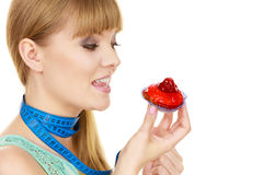 Woman holds cupcake trying to resist temptation. Woman undecided with blue measuring tape around her neck holds in hand cake cupcake, trying to resist temptation Stock Photography