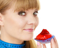 Woman holds cupcake trying to resist temptation. Woman undecided with blue measuring tape around her neck holds in hand cake cupcake, trying to resist temptation Royalty Free Stock Images