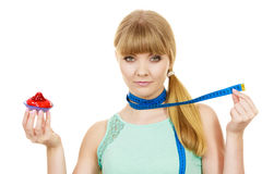 Woman holds cupcake trying to resist temptation. Woman undecided with blue measuring tape around her neck holds in hand cake cupcake, trying to resist temptation Stock Photos
