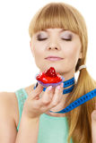 Woman holds cupcake trying to resist temptation. Woman undecided with blue measuring tape around her neck holds in hand cake cupcake, trying to resist temptation Stock Image