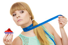 Woman holds cupcake trying to resist temptation. Woman undecided with blue measuring tape around her neck holds in hand cake cupcake, trying to resist temptation Stock Images