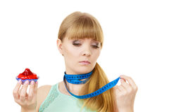 Woman holds cupcake trying to resist temptation Royalty Free Stock Image