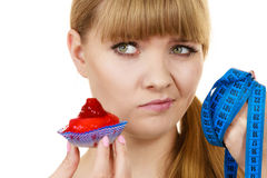 Woman holds cupcake trying to resist temptation. Woman undecided with blue measuring tape holds in hand cake cupcake, trying to resist temptation. Weight loss Royalty Free Stock Photos