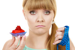 Woman holds cupcake trying to resist temptation. Woman undecided with blue measuring tape holds in hand cake cupcake, trying to resist temptation. Weight loss Royalty Free Stock Photo