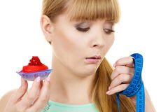 Woman holds cupcake trying to resist temptation. Woman undecided with blue measuring tape holds in hand cake cupcake, trying to resist temptation. Weight loss Royalty Free Stock Photography