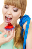 Woman holds cupcake trying to resist temptation. Woman undecided with blue measuring tape holds in hand cake cupcake, trying to resist temptation. Weight loss Stock Photos