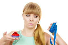 Woman holds cupcake trying to resist temptation. Woman undecided with blue measuring tape holds in hand cake cupcake, trying to resist temptation. Weight loss Stock Images
