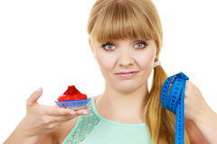 Woman holds cupcake trying to resist temptation. Woman undecided with blue measuring tape holds in hand cake cupcake, trying to resist temptation. Weight loss Stock Photography