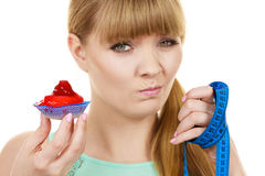 Woman holds cupcake trying to resist temptation Royalty Free Stock Images