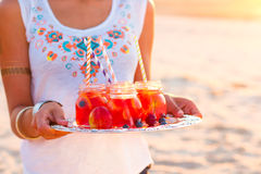 Woman holds a dish with a drinks at sunset. Picnic theme Royalty Free Stock Image